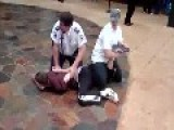 Security Guard Arresting Person Is Helped By Bystander